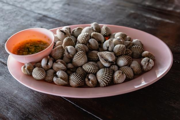 Berberechos cocidos con sabrosa salsa en el plato. Foto Premium