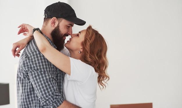 Besándose. pareja feliz juntos en su nueva casa. concepción de mudanza Foto gratis