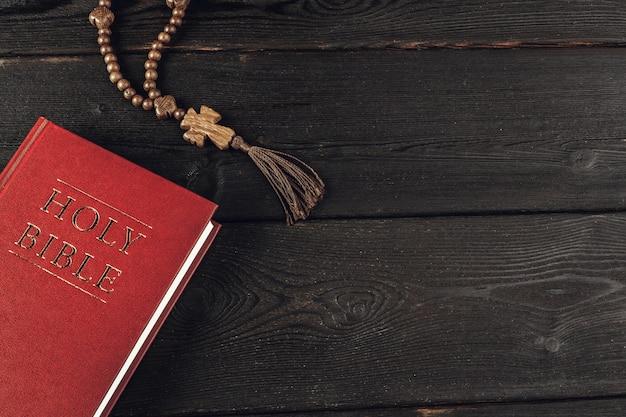 Biblia y un crucifijo en una vieja mesa de madera. concepto de religión Foto Premium