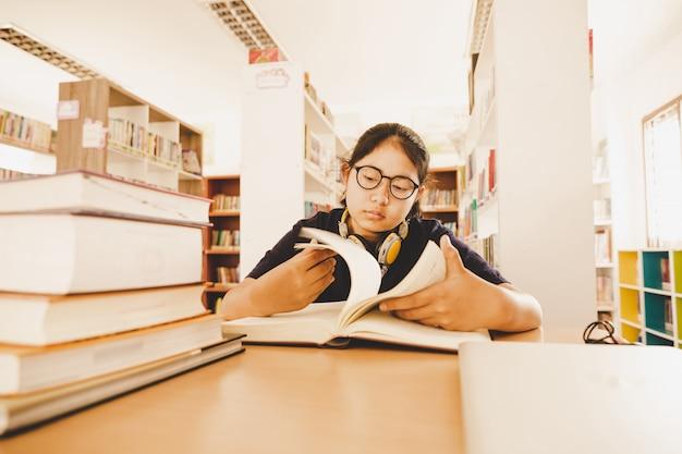 En la biblioteca - joven estudiante con libros trabajando en una biblioteca de la escuela secundaria. Foto gratis