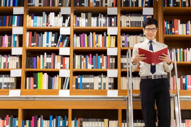 Bibliotecario de pie en las escaleras leyendo Foto Premium