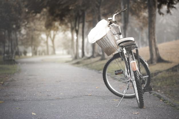 Bicicleta negra en la carretera en el parque, tono vintage. Foto Premium