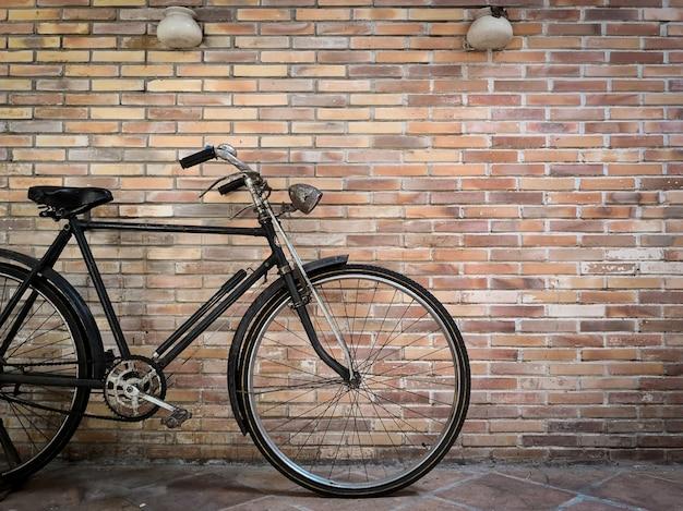 Bicicleta retra delante de la pared de ladrillo vieja. Foto Premium
