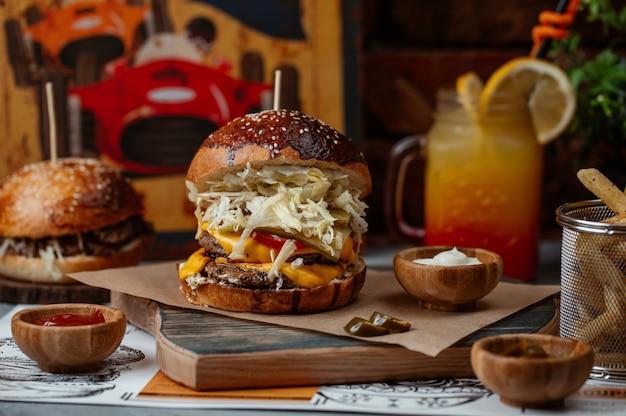 Big mac burger con carne de res, queso cheddar derretido y ensalada blanca completa Foto gratis