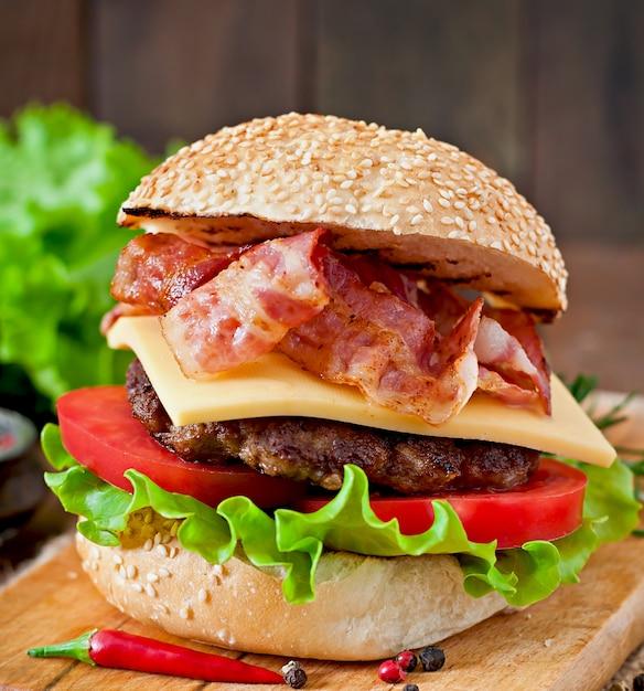 Big sandwich - hamburguesa con carne de res, queso, tomate y tocino frito Foto gratis