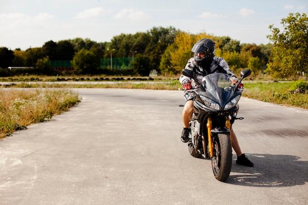 Biker cabalgando en la carretera con cuidado Foto gratis