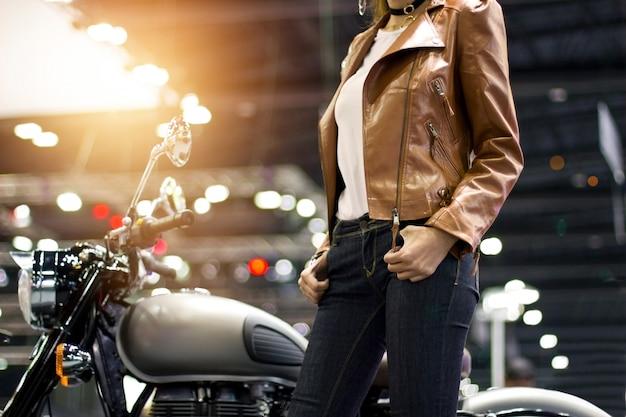 2c7241888c0 Biker mujer en una chaqueta de cuero marrón con una motocicleta en el fondo  de la calle