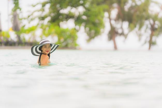 Bikini asiático hermoso joven del desgaste de la mujer del retrato alrededor de piscina en playa del océano del océano del centro turístico del hotel casi Foto gratis