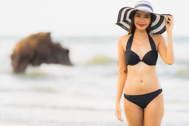 Bikini asiático joven hermoso del desgaste de mujer del retrato en el océano del mar de la playa Foto gratis