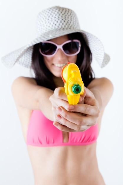 Bikini chica con pistola de chorro mirando la cámara Foto gratis
