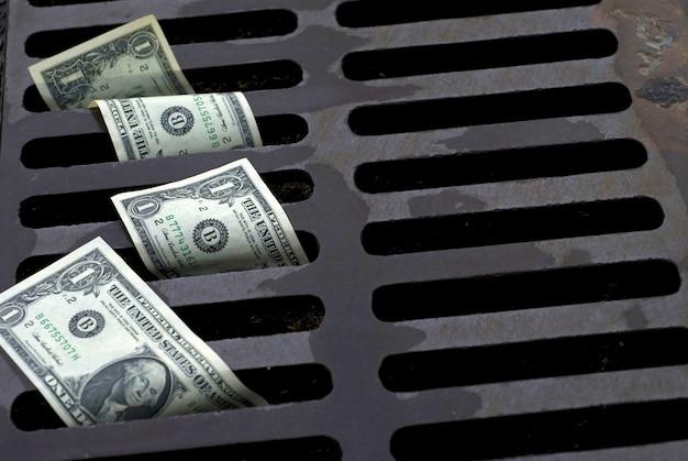 Billetes de dólar en desagüe de la calle Foto gratis