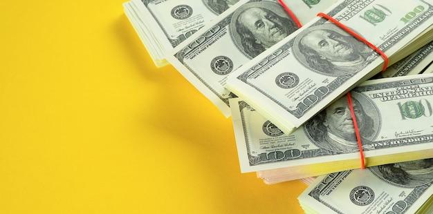 Billetes de dólares estadounidenses en paquetes sobre un fondo amarillo brillante. Foto Premium