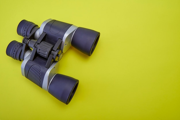 Binoculares de plata y gris sobre fondo amarillo. Foto Premium