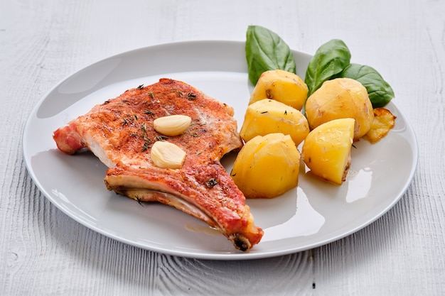 Bistec con hueso y papas al horno en una asadera con ajo y tomillo Foto Premium