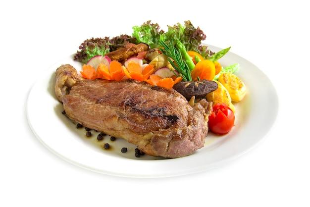 Bistec de ternera con pimientos negros decoran romero fresco, espárragos a la parrilla con hongos ostra y ensalada de rábano Foto Premium