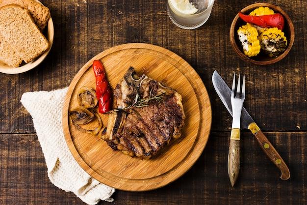 Bistec con verduras en tablero redondo. Foto gratis