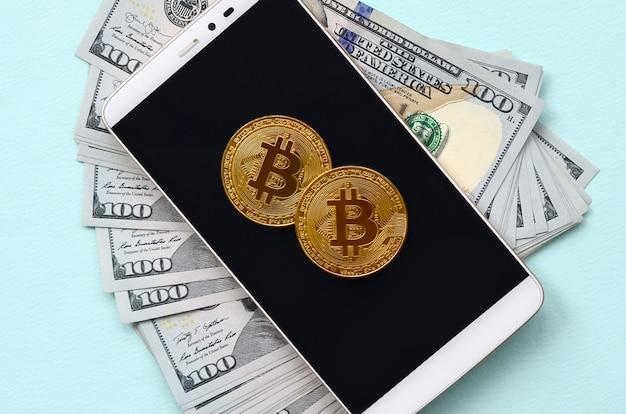 Bitcoins se encuentra en un teléfono inteligente y billetes de cien dólares sobre un fondo azul claro Foto Premium