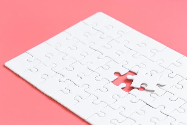 Blanco conectado piezas de rompecabezas en la pared de color rojo pastel Foto Premium