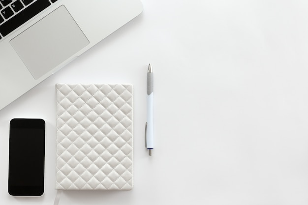 Blanco escritorio de oficina con una parte de la computadora portátil, teléfono móvil, lápiz Foto Gratis