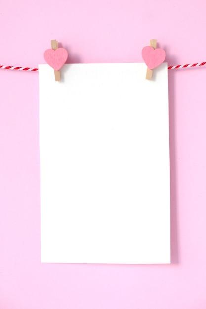 Bloc de notas en blanco del libro blanco que cuelga en fondo rosado ...