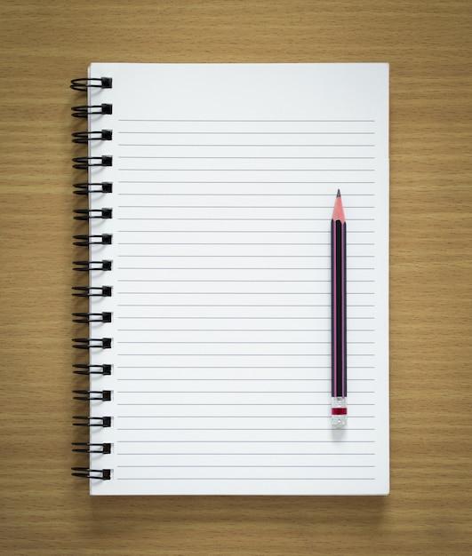 Bloc de notas espiral en blanco y lápiz sobre fondo de madera ...