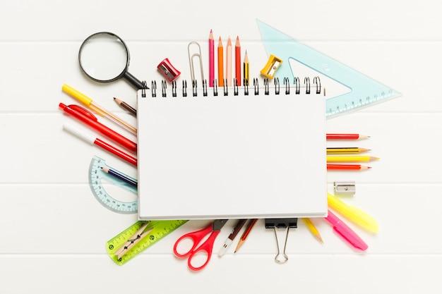Bloc de notas en blanco rodeado de útiles escolares Foto gratis