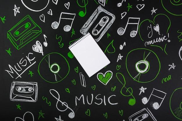 Bloc de notas en blanco sobre la pizarra con notas musicales dibujadas; cintas de casete; discos compactos Foto gratis