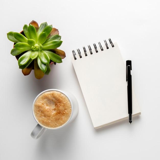 Bloc de notas con bolígrafo cerca de la taza de café Foto gratis
