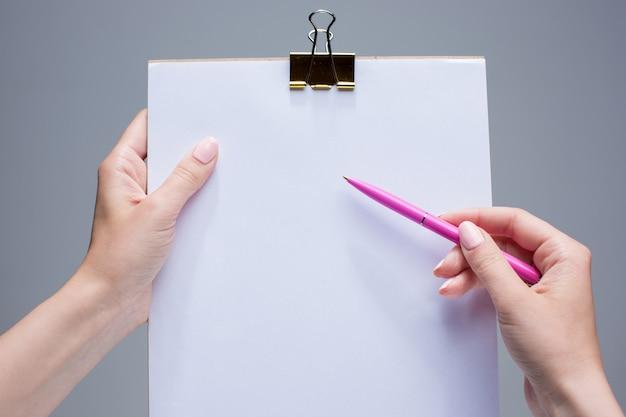 Bloc de notas y bolígrafo en manos femeninas Foto gratis