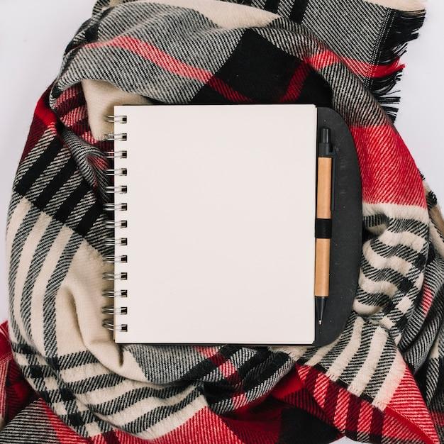 Bloc de notas en bufanda a cuadros Foto gratis