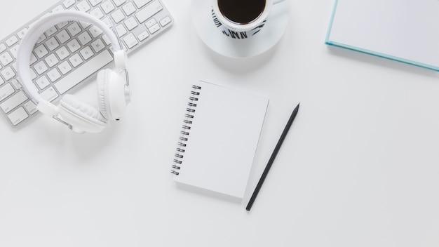 Bloc de notas cerca de aparatos electrónicos y taza de café Foto gratis