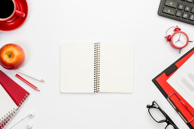 Bloc de notas espiral en blanco con papelería en escritorio de oficina Foto gratis
