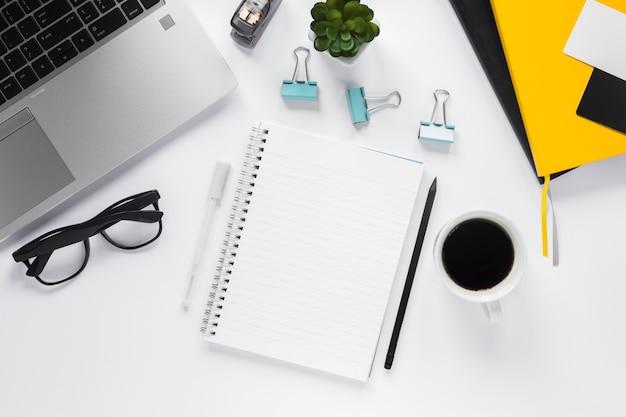 Bloc de notas espiral en blanco con taza de café y suministros de oficina en escritorio blanco Foto gratis
