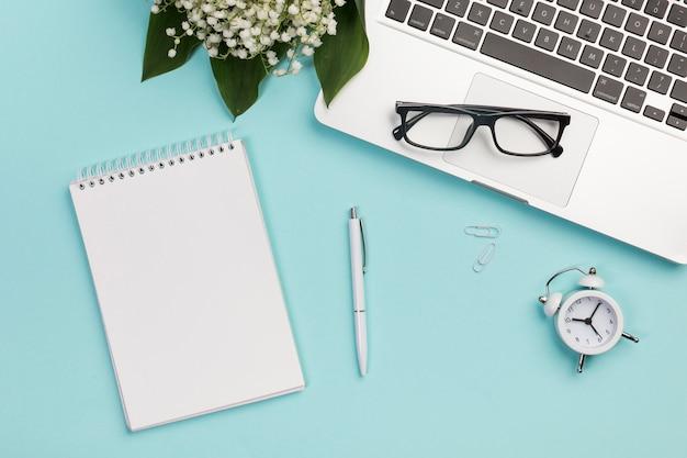 Bloc de notas en espiral, bolígrafo, sujetapapeles, reloj despertador, anteojos en una computadora portátil con un ramo de flores de lirio de los valles en un escritorio de negocios azul Foto gratis