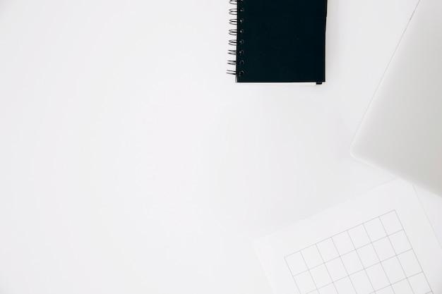 Bloc de notas en espiral; portátil y página aislados sobre fondo blanco Foto gratis