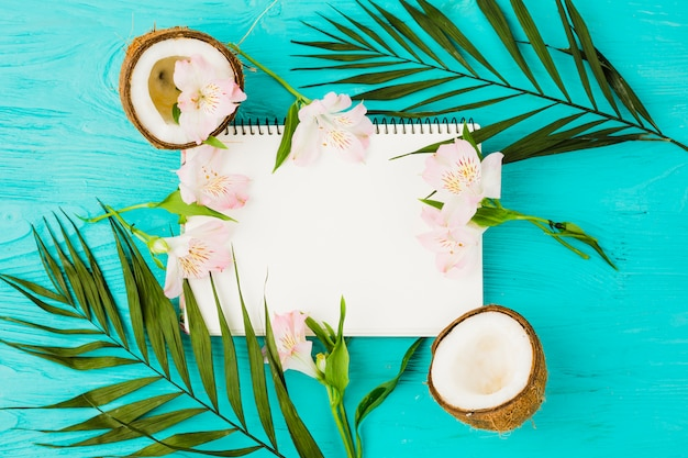 Bloc de notas entre hojas de planta con cocos frescos y flores. Foto gratis