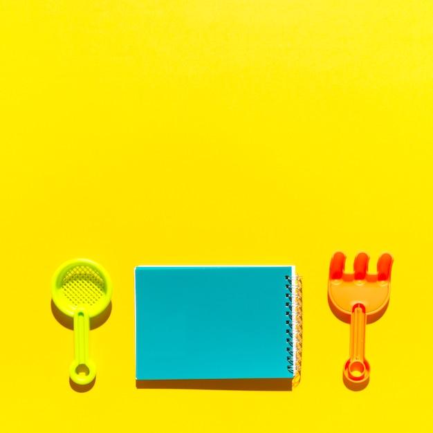 Bloc de notas y rastrillo en superficie colorida Foto gratis