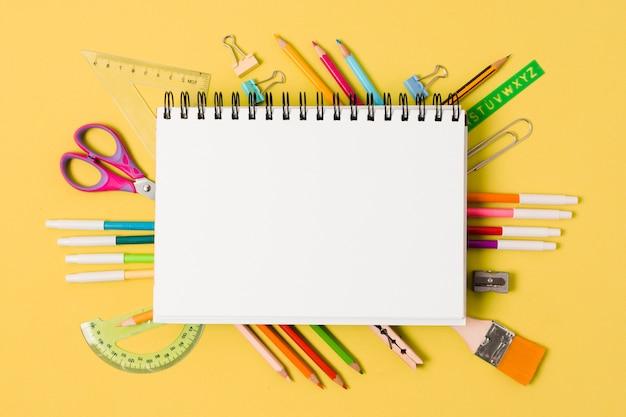 Bloc de notas rodeado de útiles escolares Foto gratis
