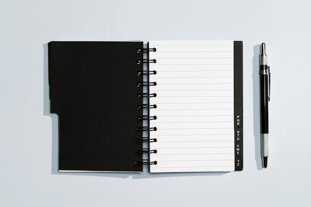 Bloc de notas con tapas negras y bolígrafo Foto gratis