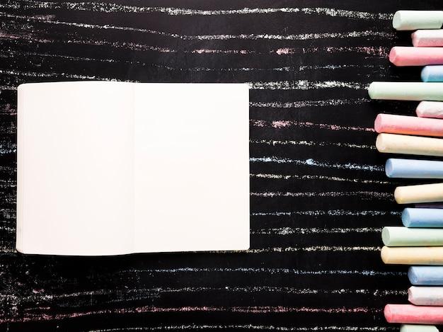 Bloc de notas con tiza en tablero negro Foto gratis