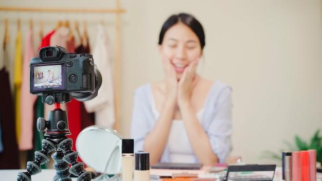 La blogger de belleza presenta cosméticos de belleza que se sientan en la cámara frontal para grabar video. Foto gratis