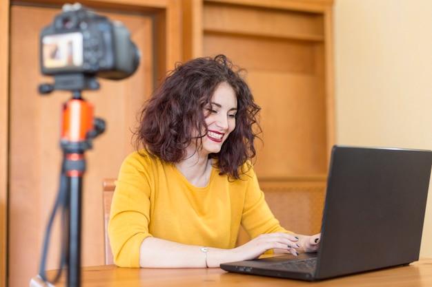 Blogger morena escribiendo en el portátil Foto gratis