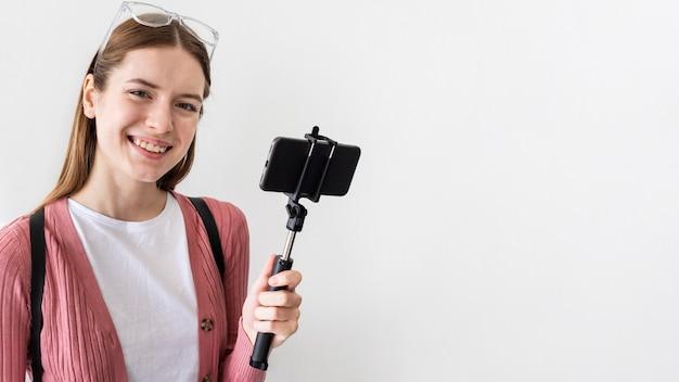 Blogger sonriente con smartphone con espacio de copia Foto gratis