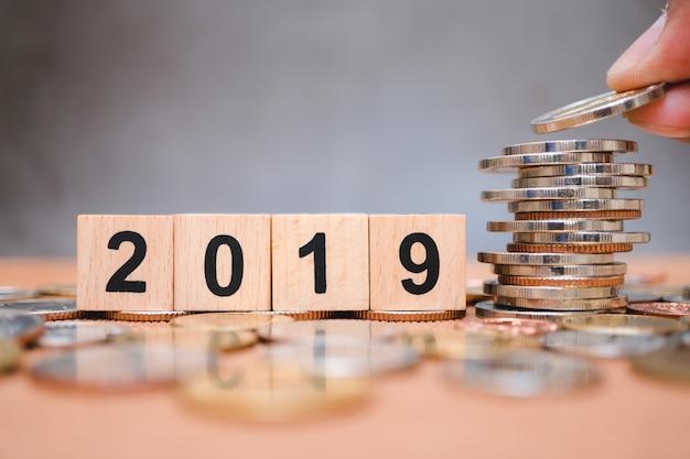 Bloque de madera año 2019 con la mano que sostiene la pila de monedas Foto Premium