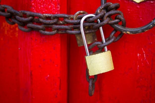 Bloqueo viejo bloqueado en una puerta roja de madera con cierre oxidado de la cadena para arriba. Foto Premium