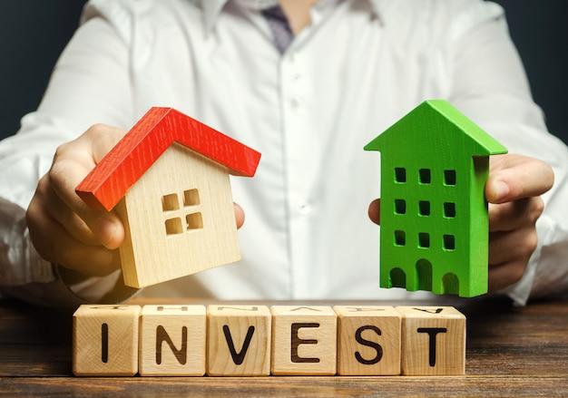 Bloques de madera con la palabra invertir y casas Foto Premium
