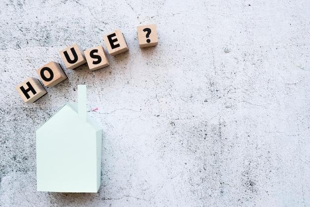Los bloques del modelo de casa con signo de interrogación firman sobre el modelo de papel contra la pared blanca del grunge Foto gratis