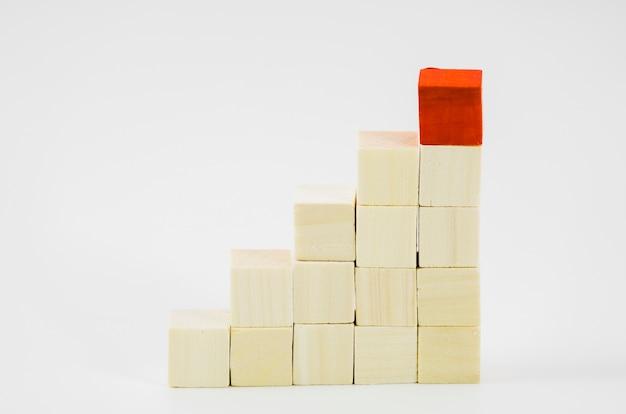 Bloques rojos sobre el fondo de madera apilados sobre fondo blanco Foto gratis