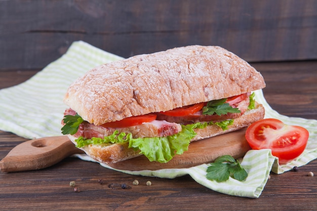 Bocadillo con el jamón y las verduras en un fondo de madera oscuro. Foto Premium