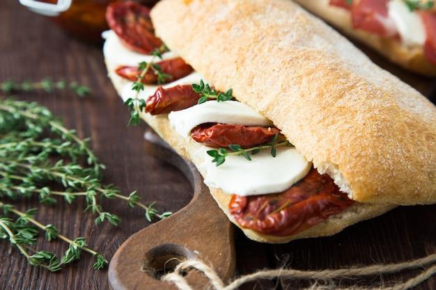 Bocadillos surtidos. sándwich caprese con mozzarella y tomates secos y ciabatta con jamón Foto Premium